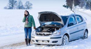 Девушка стоит у машины с открытым капотом