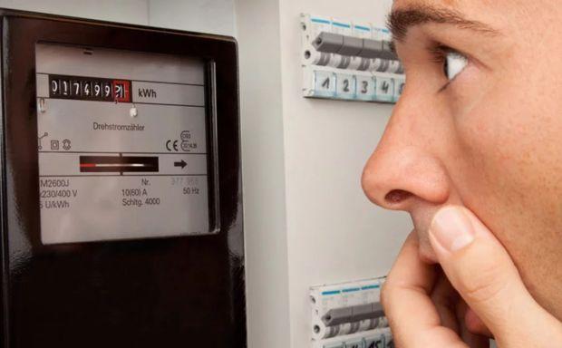 Мужчина смотрит показания счетчика электроэнергии