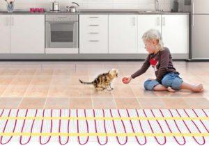 Ребенок играет с котенком на теплом полу