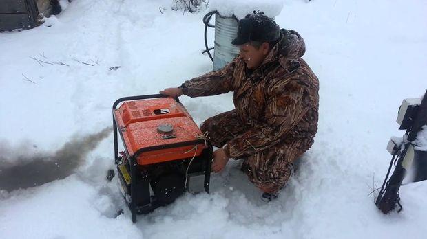 Мужчина заводит бензиновый генератор в мороз