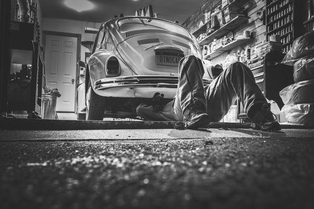 Мужчина чинит машину в гараже